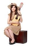 妇女坐她的手提箱,当弹吉他时 免版税库存照片