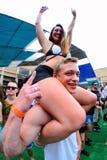 妇女坐她的男朋友肩膀在生波探侧器节日 库存图片
