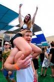妇女坐她的男朋友肩膀在生波探侧器节日 免版税库存图片