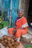 妇女坐她的门阶卖一些个椰子 免版税库存照片