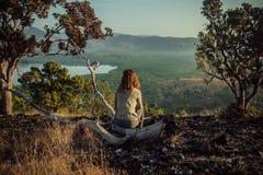 妇女坐小山在日出 免版税库存图片