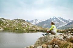 妇女坐岩石在山湖 图库摄影