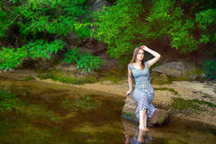 妇女坐岩石在池塘 库存图片
