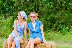 妇女坐干草堆在乡下 免版税库存照片