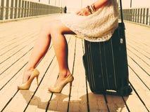 妇女坐手提箱,码头在背景中 库存图片