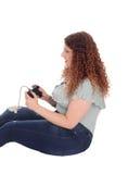 妇女坐打她的电子游戏的地板 库存照片