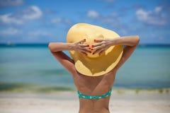 妇女坐拿着帽子的海滩 库存照片