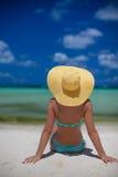 妇女坐拿着帽子的海滩 库存图片