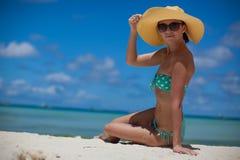 妇女坐拿着帽子的海滩 免版税库存图片