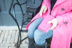 妇女坐拿着桃红色钱包的长凳 库存照片
