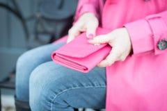 妇女坐拿着桃红色钱包的长凳 库存图片