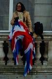 妇女坐拿着英国旗子的小被雕刻的篱芭在事件期间在城市 免版税库存图片