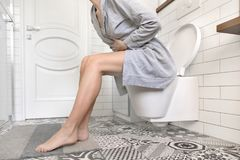 妇女坐握她的胃的洗手间 免版税库存照片
