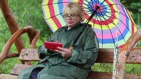 妇女坐摇摆长凳并且使用红色智能手机 影视素材