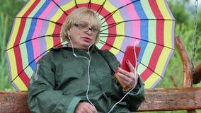 妇女坐摇摆长凳并且通过智能手机沟通 股票录像