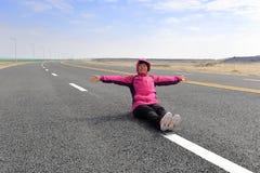 妇女坐新的路在冬天 免版税库存图片