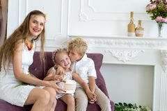妇女坐有她的儿子和女儿的长沙发 免版税库存图片