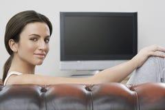 妇女坐有平面屏幕电视的沙发在背景中 免版税库存图片