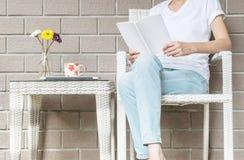 妇女坐木织法椅子在读的一本白皮书房子在业余时间下午,放松时期和生活方式  免版税库存图片