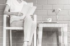 妇女坐木织法椅子在读的一本白皮书房子在业余时间下午,放松时期和生活方式  免版税图库摄影