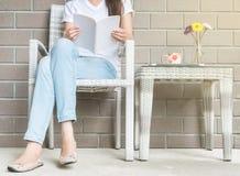 妇女坐木织法椅子在读的一本白皮书房子在业余时间下午,放松时期和生活方式  库存图片