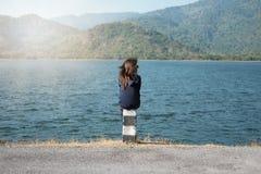 妇女坐柱子路旁前面她有大湖和 库存照片