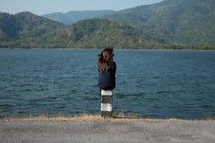 妇女坐柱子路旁前面她有大湖和 库存图片