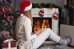 妇女坐毛茸的地毯在壁炉和圣诞树附近 免版税库存照片