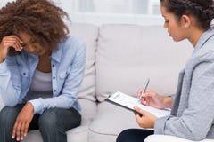 妇女坐沙发在疗法 库存照片