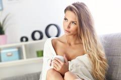 妇女坐沙发用咖啡 免版税库存图片