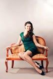妇女坐沙发 免版税库存照片