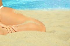 妇女坐沙子在海滩 免版税库存图片