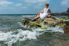妇女坐海滨 库存图片