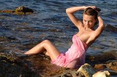 妇女坐海滩 免版税库存照片