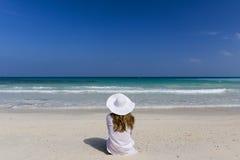 妇女坐海滩 免版税库存图片