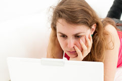 妇女坐满意对膝上型计算机 库存照片