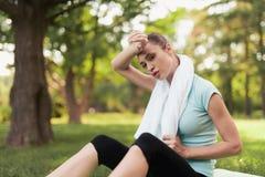 妇女坐瑜伽的一个地毯并且在锻炼以后休息 在她后是瑜伽的一个蓝色球 免版税库存照片
