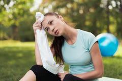 妇女坐瑜伽的一个地毯并且在锻炼以后休息 在她后是瑜伽的一个蓝色球 库存图片