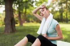 妇女坐瑜伽的一个地毯并且在锻炼以后休息 在她后是瑜伽的一个蓝色球 库存照片