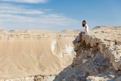 妇女坐的沙漠山边缘 免版税库存照片
