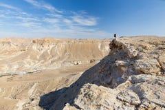 妇女坐的沙漠山边缘 库存图片
