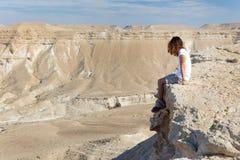 妇女坐的沙漠山边缘 图库摄影