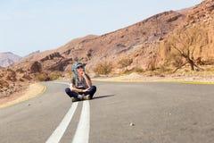 妇女坐的沥青沙漠路 库存图片