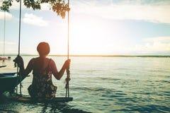 妇女坐的海滩在美丽摇摆 免版税库存照片