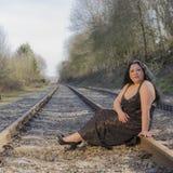 妇女坐看您的火车轨道 免版税库存图片