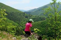 妇女坐看美好的绿色山景的峭壁边缘 免版税库存照片