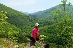 妇女坐看美好的绿色山景的峭壁边缘 图库摄影