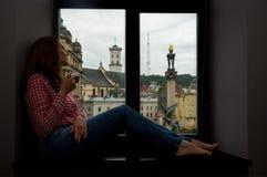 妇女坐窗台 库存照片
