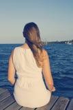 妇女坐船坞,看往海洋 免版税库存图片