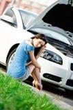 妇女坐草在她残破的汽车附近 免版税图库摄影